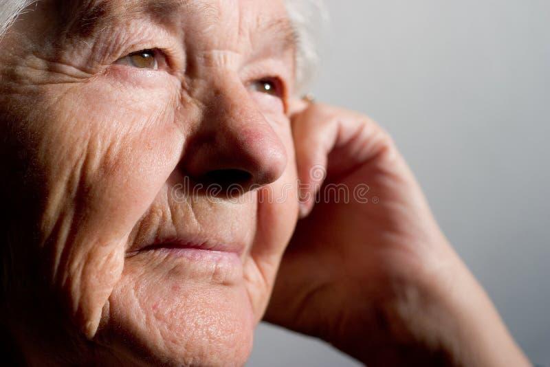 Donna anziana che contempla fotografie stock