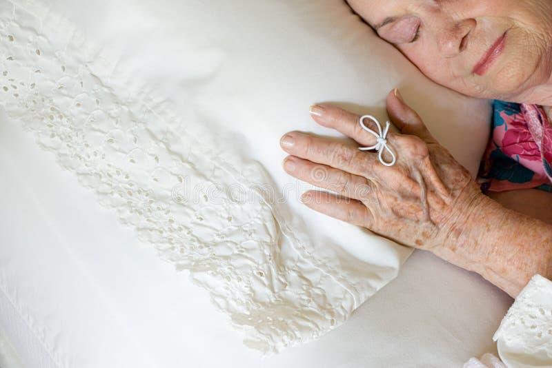 Donna anziana che dorme con la corda sul suo dito fotografia stock libera da diritti