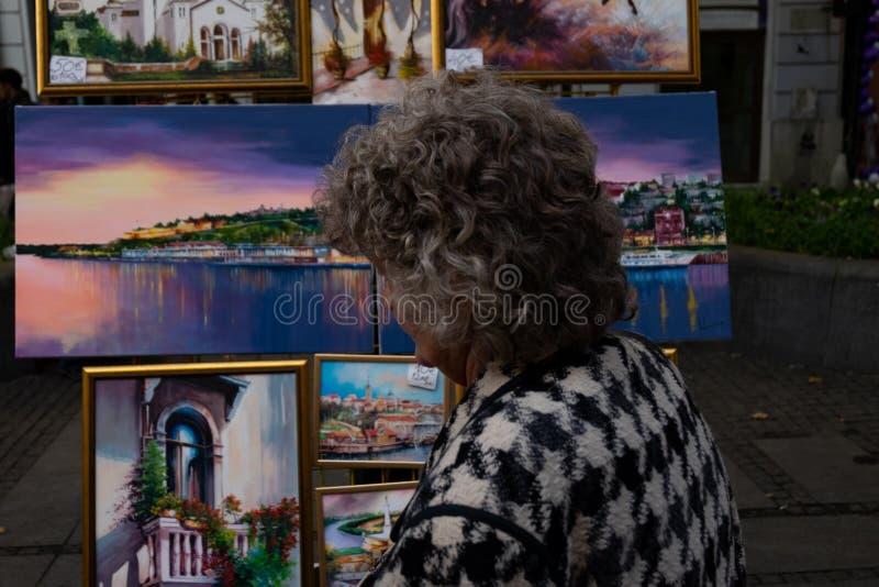 Donna anziana che esamina le pitture immagini stock libere da diritti