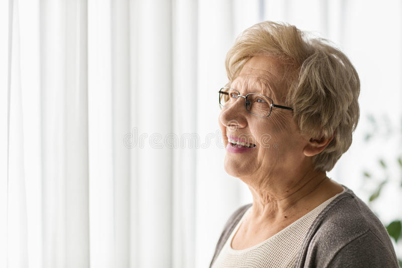 Donna anziana che guarda attraverso una finestra immagini stock libere da diritti