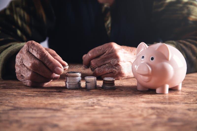 Donna anziana che impila le monete sulla tavola di legno fotografia stock