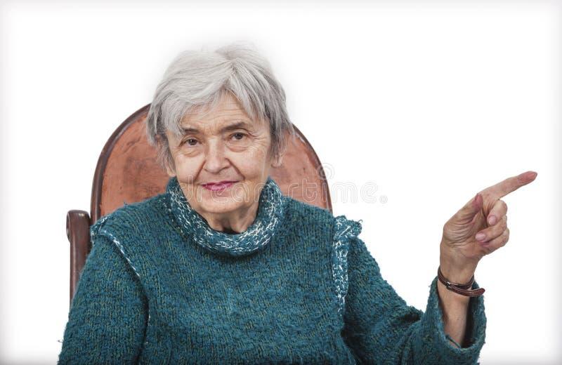 Donna anziana che indica il suo dito qualcosa fotografie stock