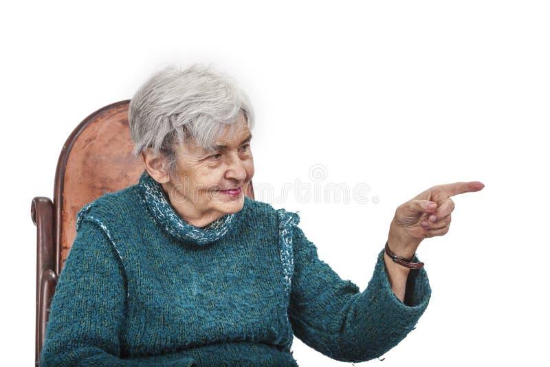 Donna anziana che indica il suo dito qualcosa fotografia stock libera da diritti