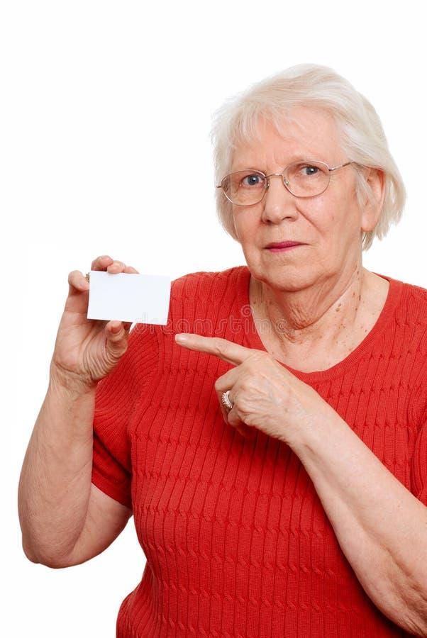 Donna anziana che indica un biglietto da visita fotografia stock