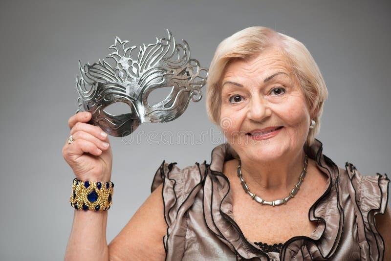 Donna anziana che indossa maschera affascinante immagine stock