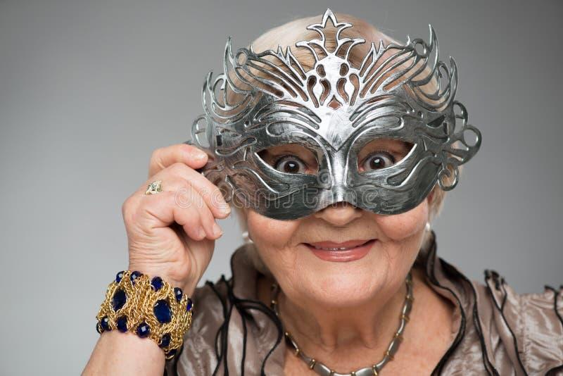 Donna anziana che indossa maschera affascinante immagine stock libera da diritti