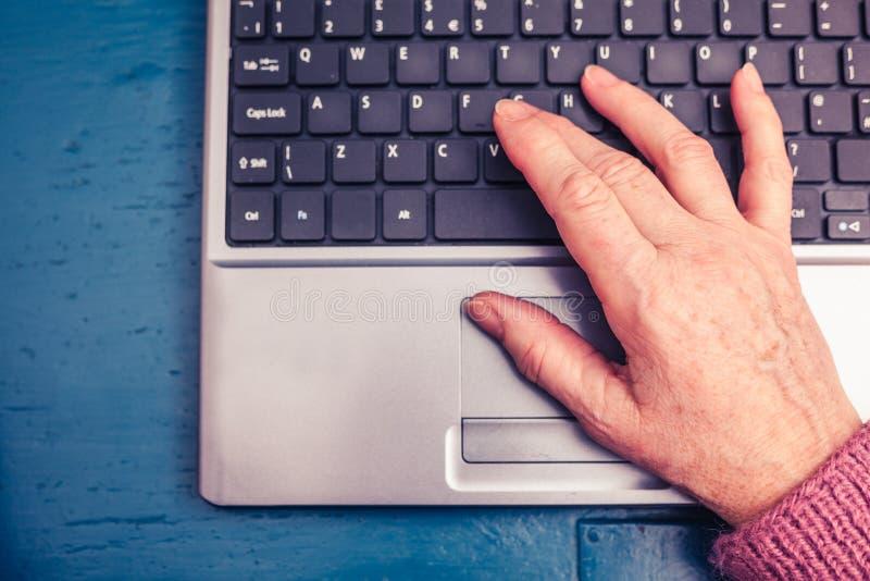 Donna anziana che lavora al computer portatile a casa fotografie stock libere da diritti
