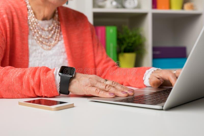 Donna anziana che lavora all'ufficio con il computer portatile fotografia stock libera da diritti