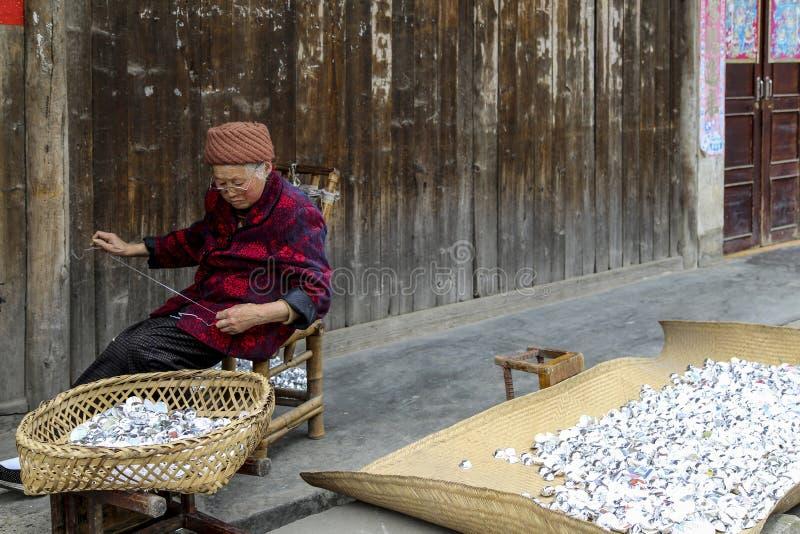 Donna anziana che lavora in una città, porcellana immagine stock