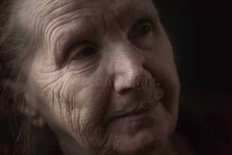 Donna anziana che pensa nello scuro immagini stock libere da diritti