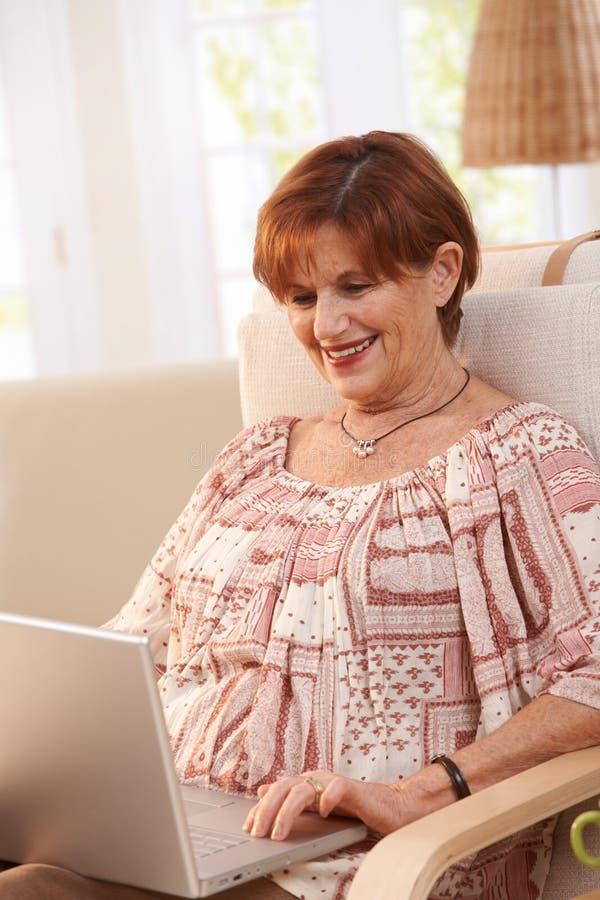 Donna anziana che per mezzo del computer portatile fotografia stock libera da diritti