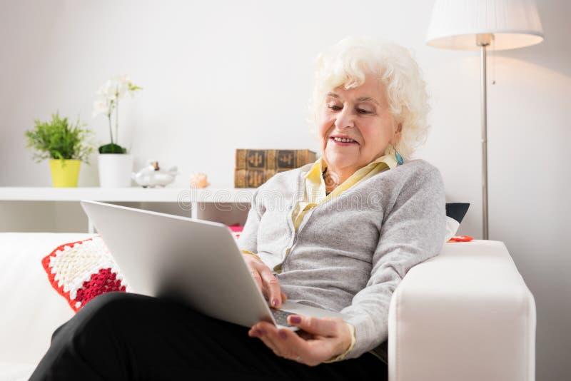 Donna anziana che per mezzo del computer portatile fotografia stock