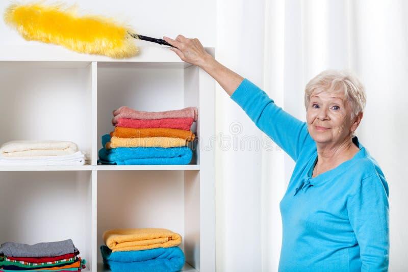 Donna anziana che per mezzo dello spolveratore fotografia stock