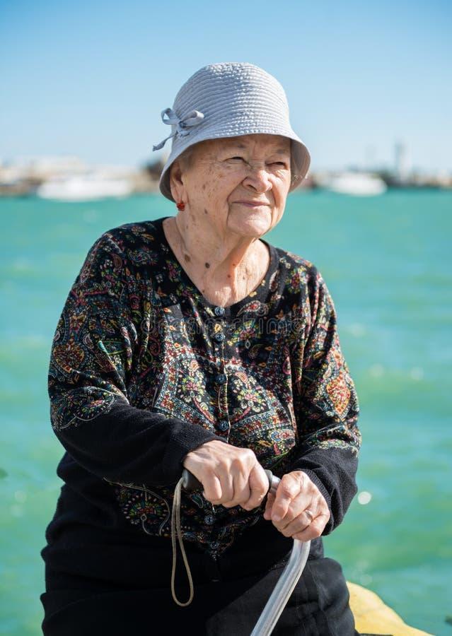 Donna anziana che posa con una canna vicino al mare immagine stock