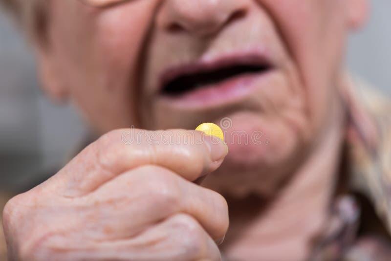 Donna anziana che prende farmaco immagine stock