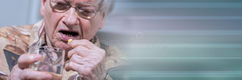 Donna anziana che prende farmaco; insegna panoramica immagine stock