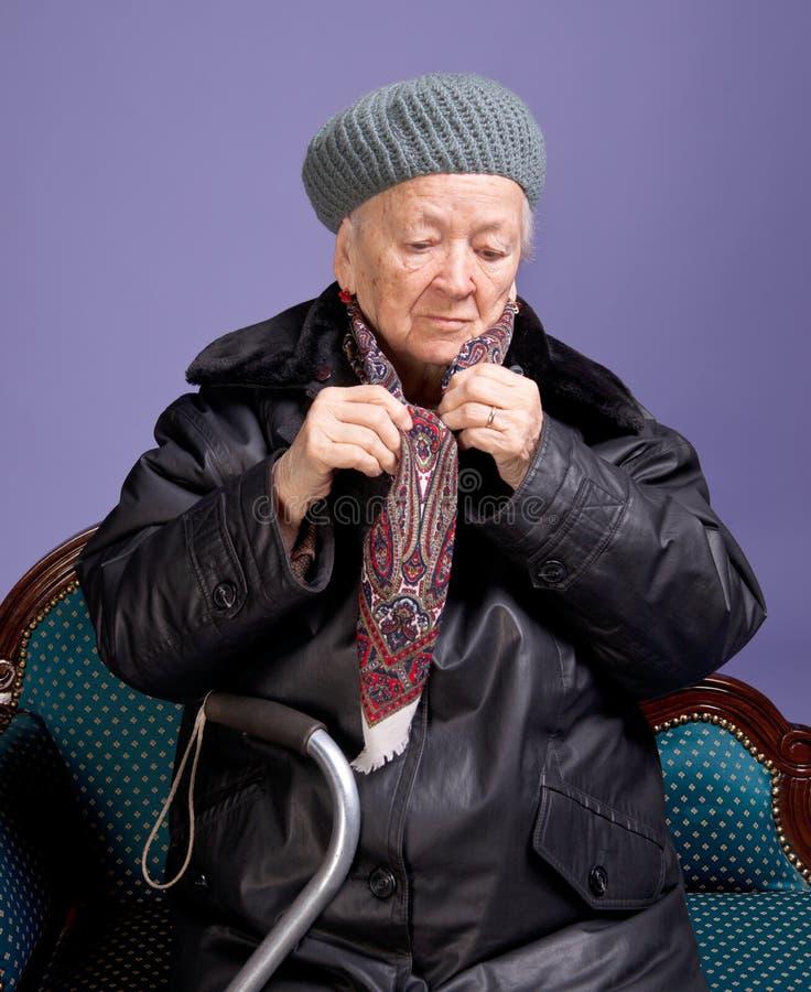 Donna anziana che regola la sua sciarpa fotografia stock libera da diritti
