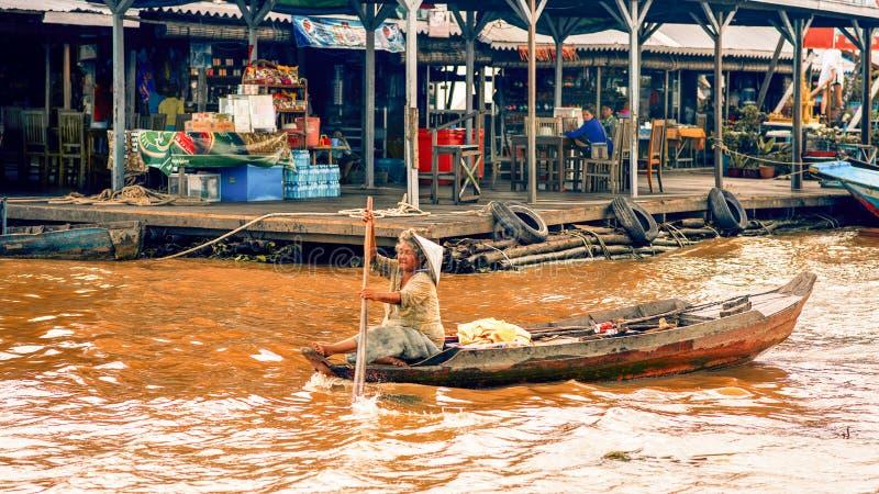 Donna anziana che rema una barca sul lago sap di Tonle immagini stock