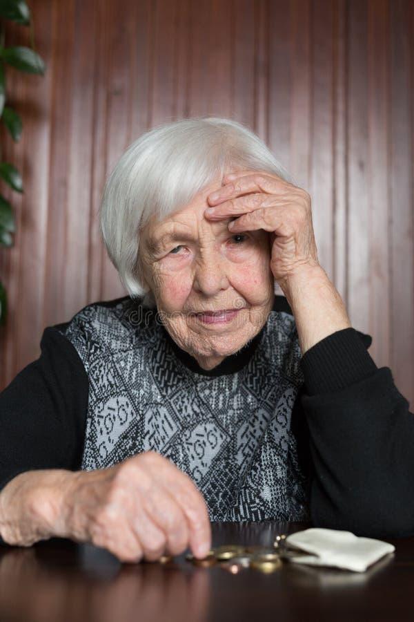Donna anziana che si siede alla tavola che conta soldi in suo portafoglio fotografie stock