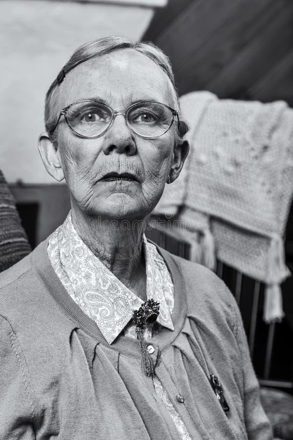 Donna anziana che si siede diritto fotografia stock
