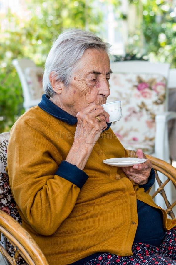 Donna anziana che si siede e che beve caffè turco nel balcone un giorno soleggiato immagine stock libera da diritti