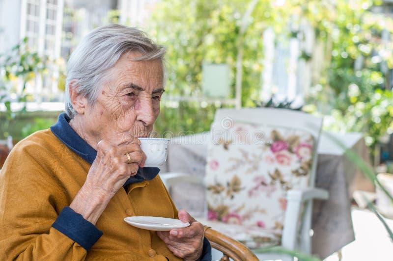 Donna anziana che si siede e che beve caffè turco nel balcone un giorno soleggiato immagine stock
