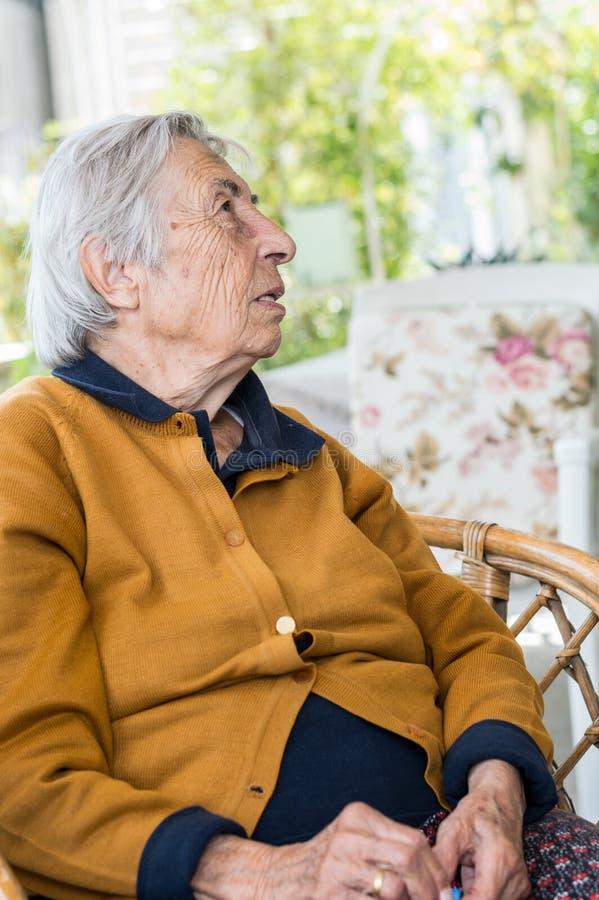 Donna anziana che si siede nel balcone che ha conversazione con la sua famiglia fotografia stock libera da diritti
