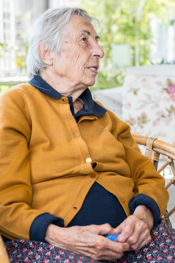 Donna anziana che si siede nel balcone che ha conversazione con la sua famiglia fotografie stock libere da diritti