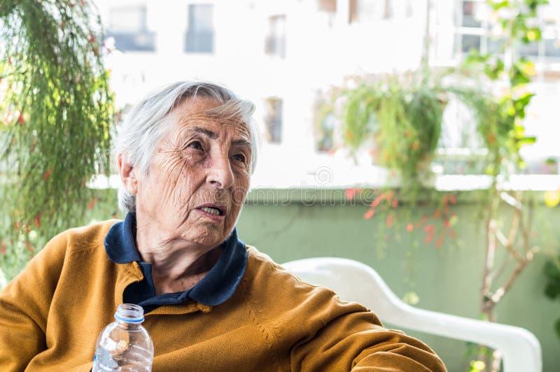 Donna anziana che si siede nel balcone che ha conversazione con la sua famiglia fotografia stock