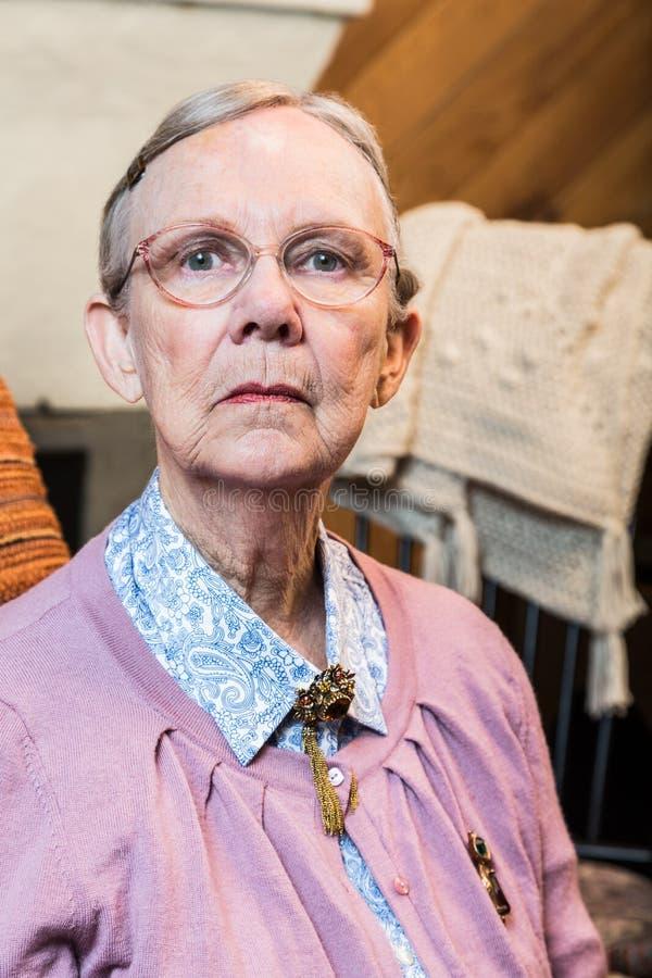 Donna anziana che si siede severo fotografia stock libera da diritti