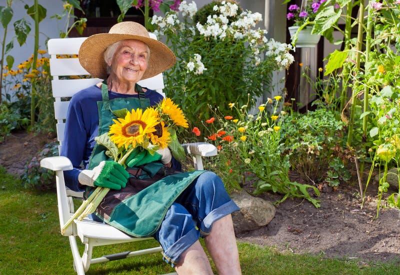 Donna anziana che si siede sui girasoli di una tenuta della sedia fotografia stock libera da diritti