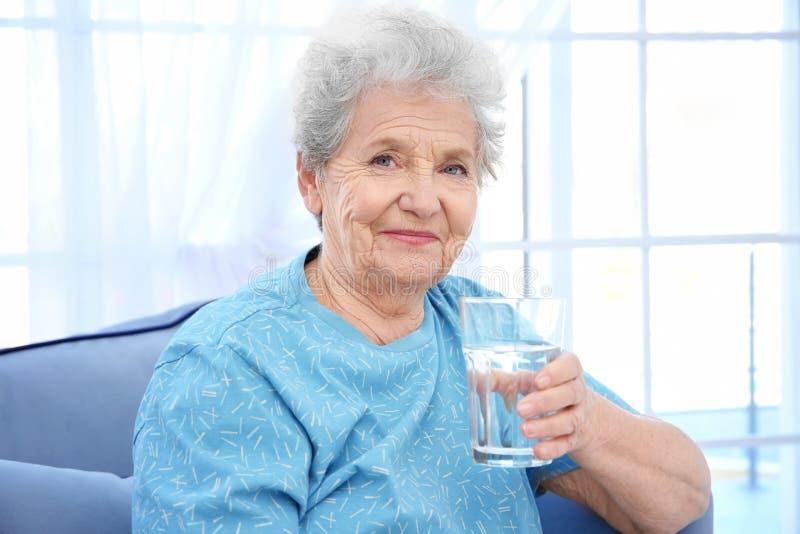 Donna anziana che si siede sullo strato e che tiene bicchiere d'acqua fotografia stock libera da diritti