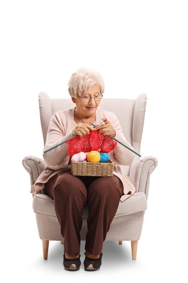 Donna anziana che si siede in una poltrona ed in un tricottare immagine stock