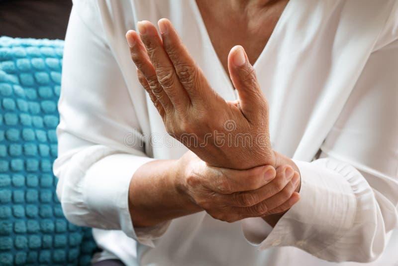 Donna anziana che soffre dal dolore della mano del polso, concetto di problema sanitario immagini stock libere da diritti