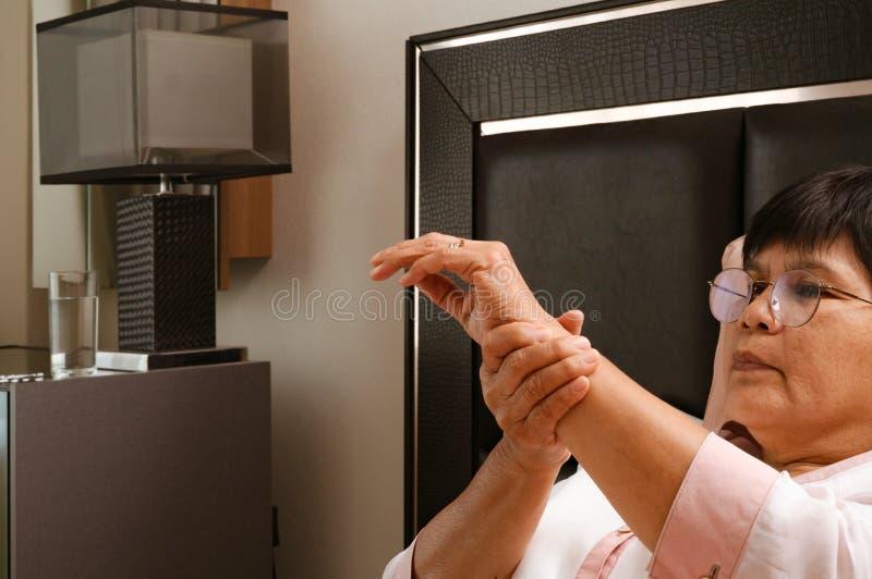 Donna anziana che soffre dal dolore della mano del polso, concetto di problema sanitario fotografia stock libera da diritti