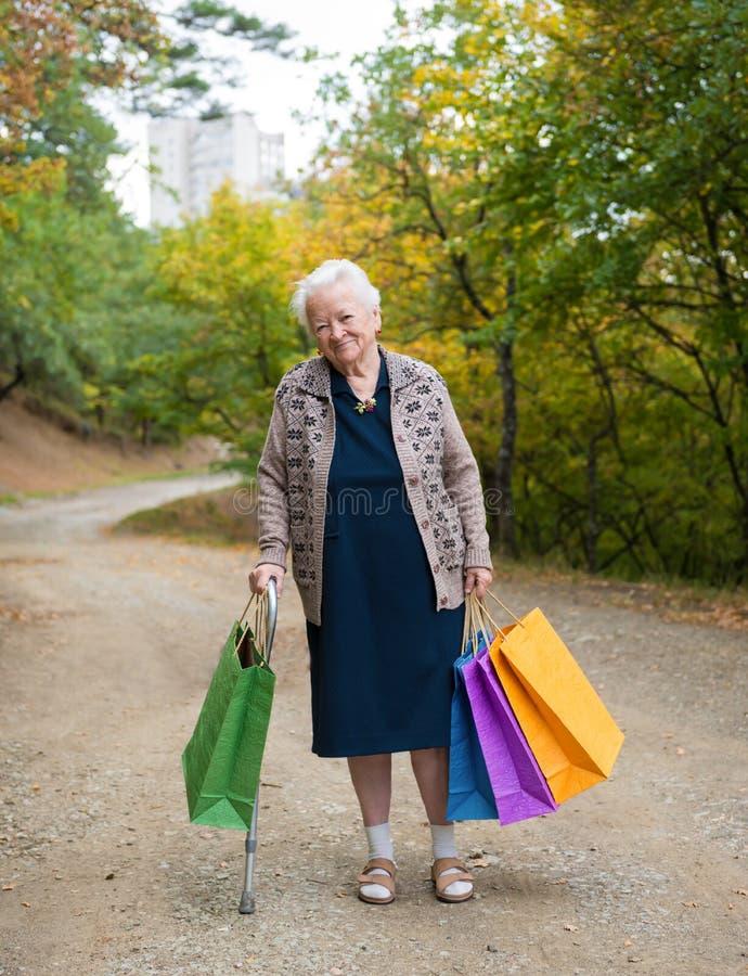 Donna anziana che sta con i sacchetti della spesa fotografie stock libere da diritti
