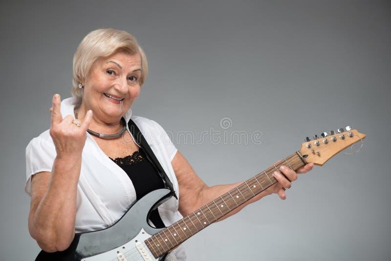 Donna anziana che tiene la chitarra fotografie stock libere da diritti