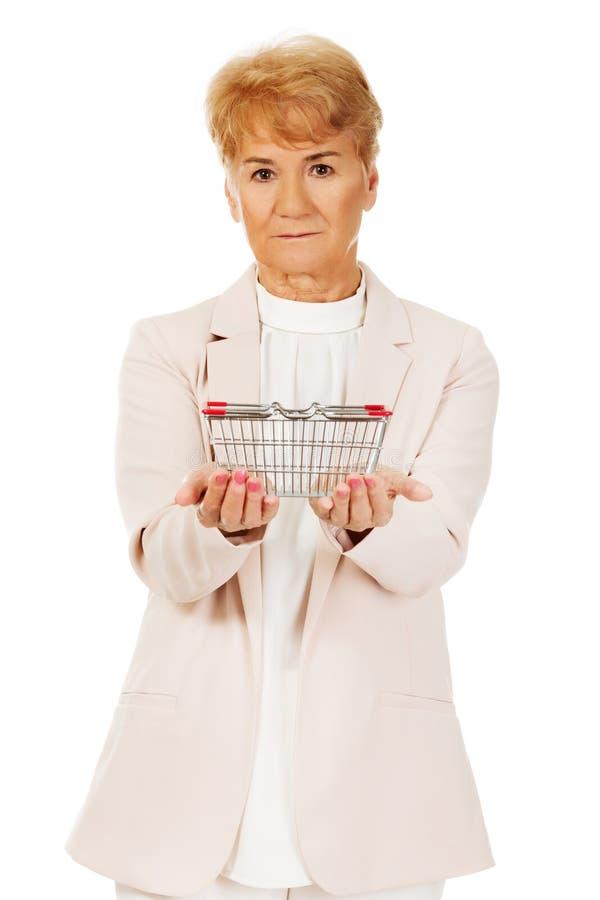 Donna anziana che tiene piccolo cestino della spesa immagini stock libere da diritti