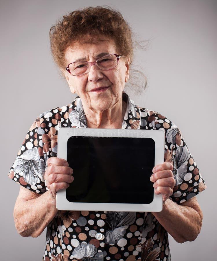 Donna anziana che tiene una compressa nelle mani di immagini stock