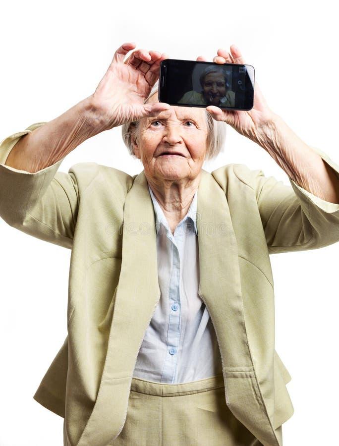 Donna anziana che usando cellulare per la presa del selfie fotografie stock
