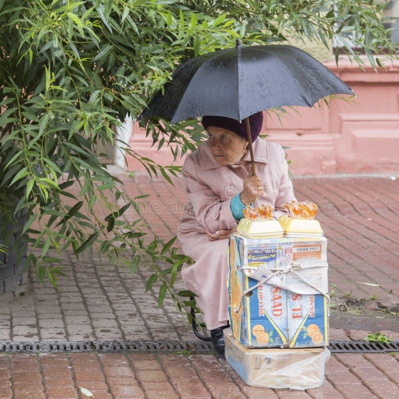 Donna anziana che vende artware nella pioggia in Nižnij Novgorod, Federazione Russa fotografia stock