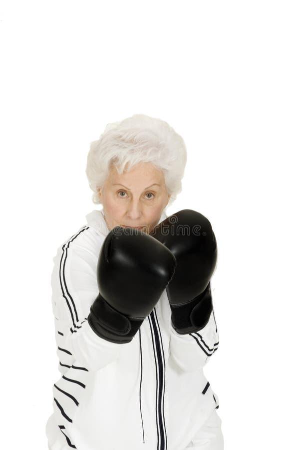 Donna anziana con i guanti di inscatolamento immagini stock