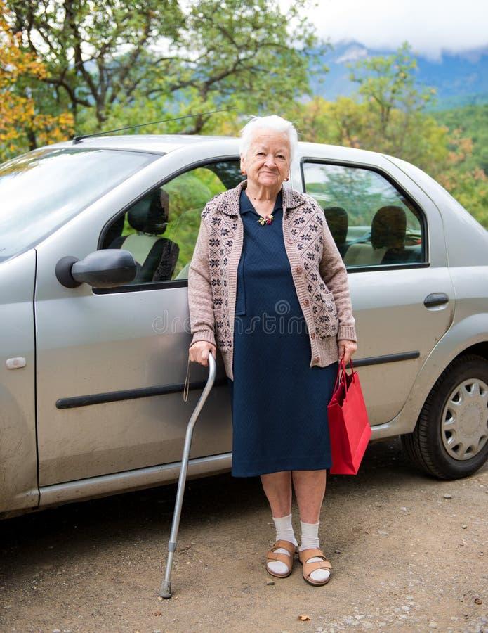 Donna anziana con i sacchetti della spesa immagini stock