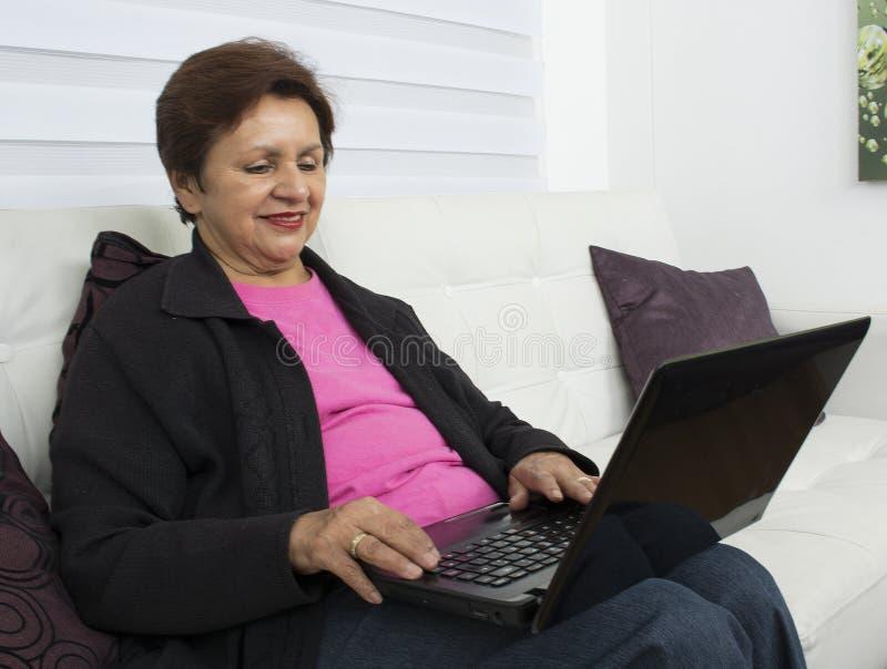 Donna anziana con il computer portatile immagini stock libere da diritti