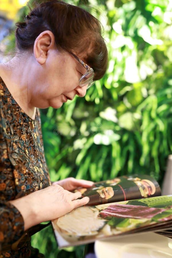 Donna anziana con il libro del menu immagine stock libera da diritti