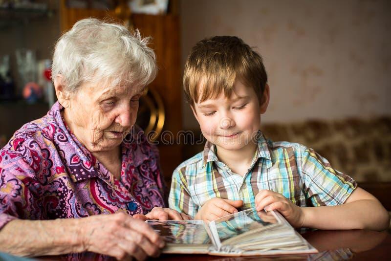 Donna anziana con il suo piccolo nipote che guarda album famiglia fotografia stock