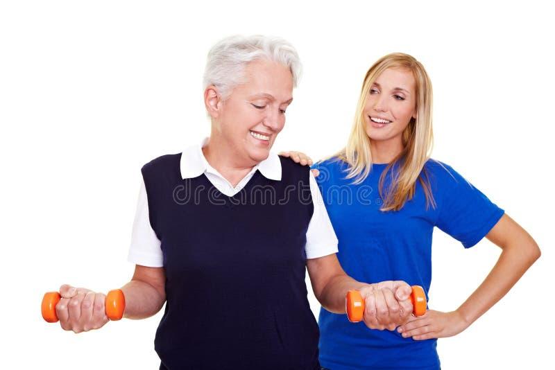 Donna anziana con l'addestratore personale immagine stock libera da diritti