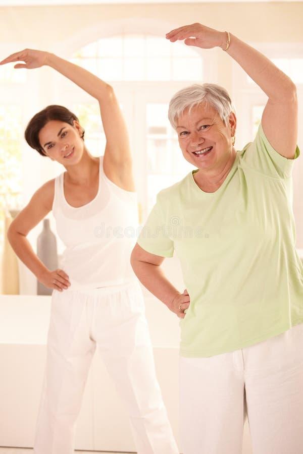 Donna anziana con l'addestratore personale di forma fisica fotografia stock