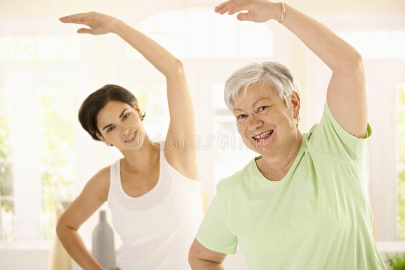 Donna anziana con l'addestratore personale di forma fisica immagini stock