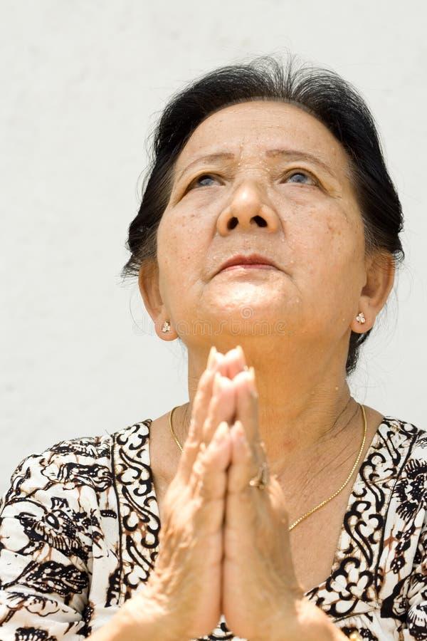 Donna anziana con l'atteggiamento di culto immagini stock libere da diritti